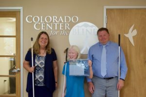 Sixth-grader Chloe stands between Julie and Brent with the tactile CCB logo behind them.