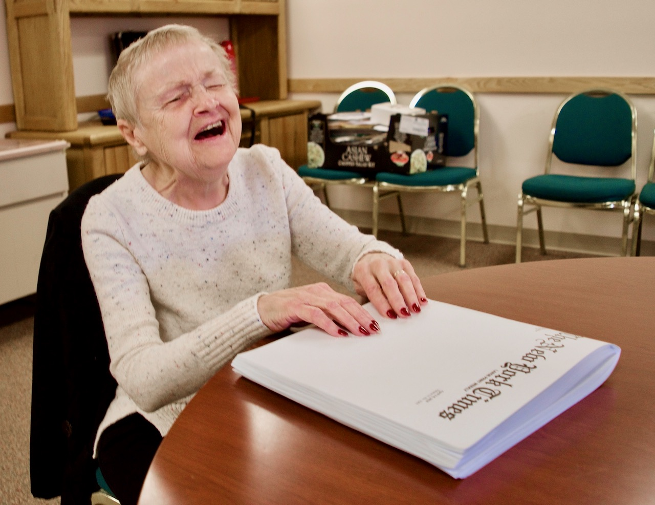 A small blind woman laughs as her hands rest on a Braille copy of the New York Times Weekly.