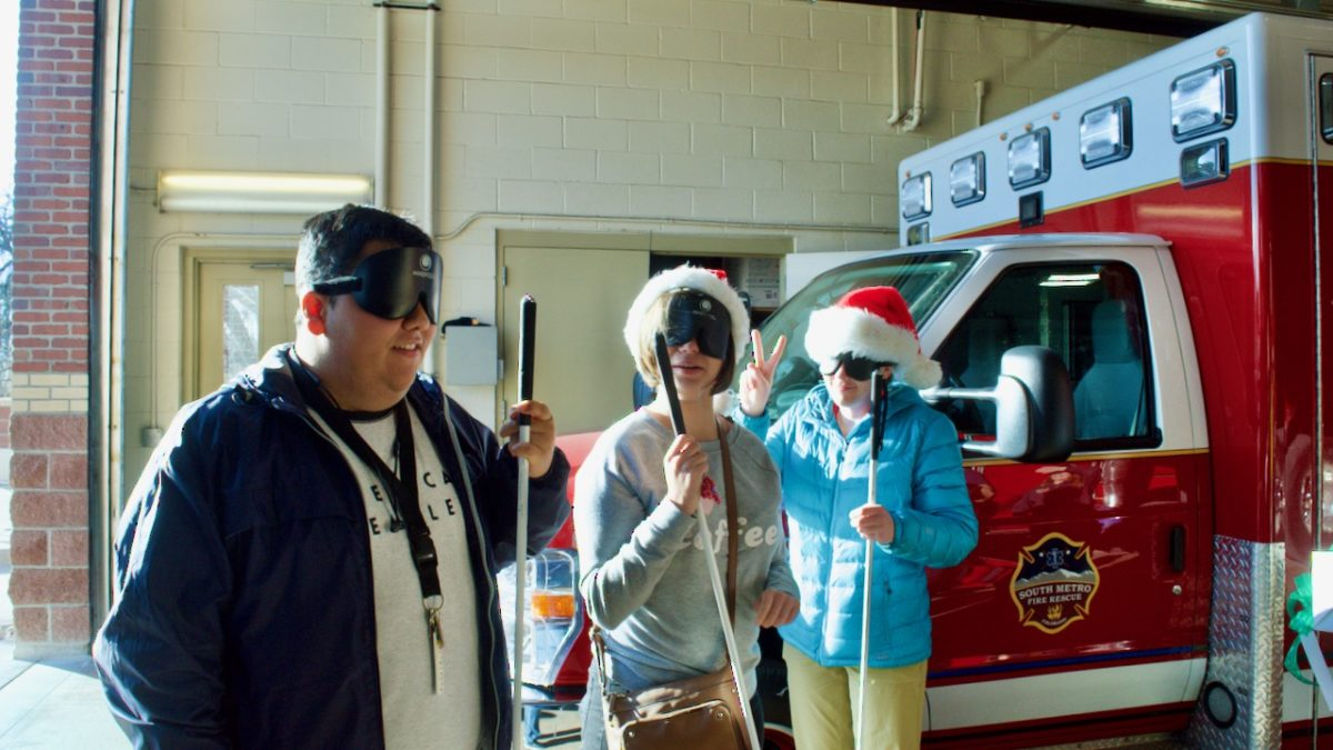 Three young students stand in front of a medical vehicle, all wearing Santa hats