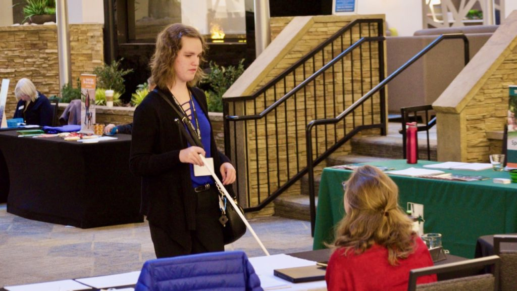 A young woman holding a white cane faces us as she talks to a vendor.