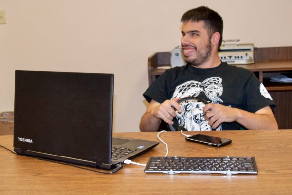 CCB Summer Tech Instructor engaged with his laptop and Smart Phone