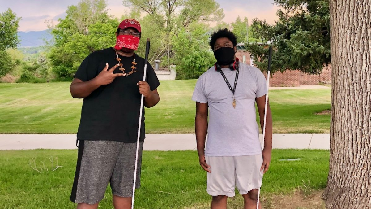 Two young Black men wearing COVID masks and holding white canes stand under leafy trees.