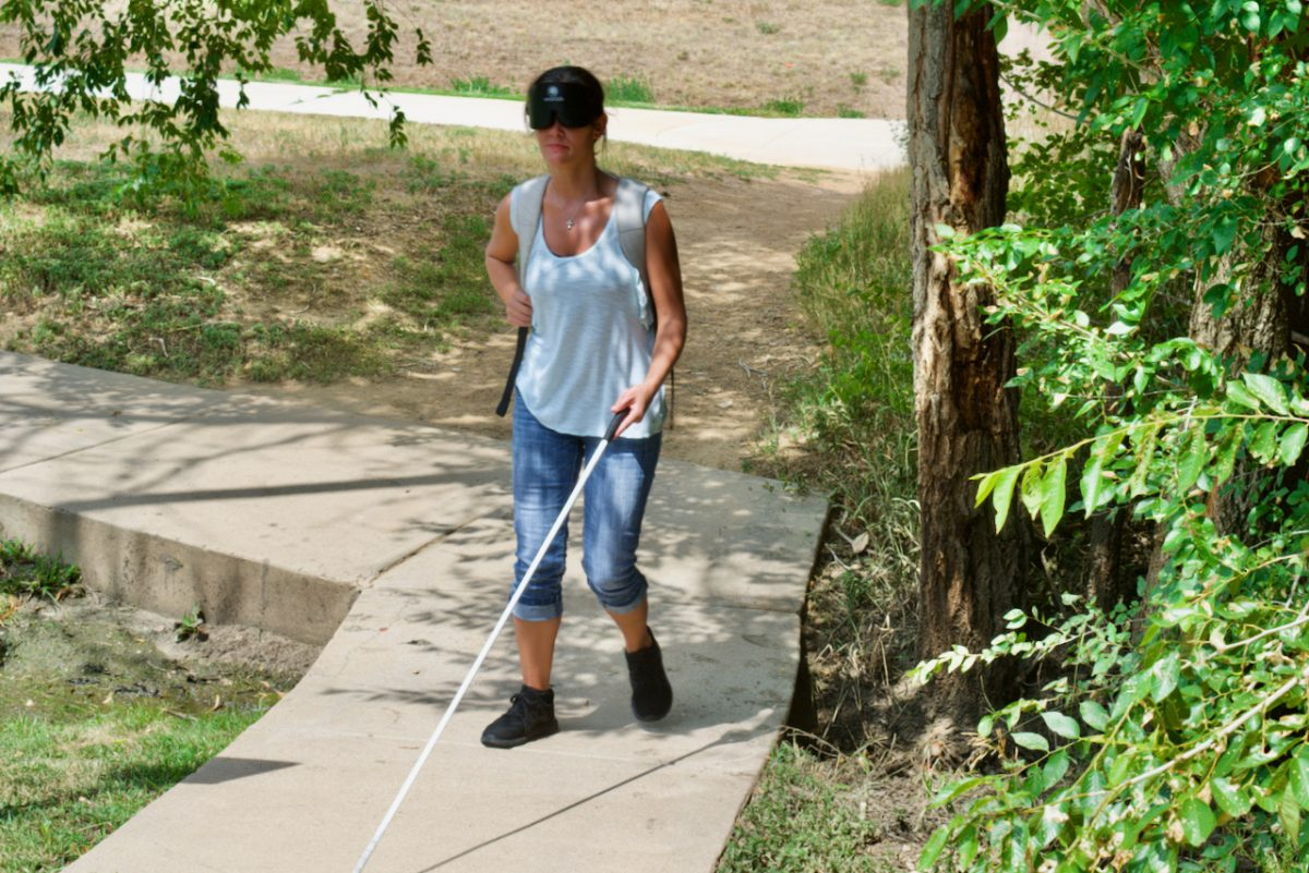 A woman wearing sleepshades and backpack walks uphill on a narrow sidewalk with her white cane