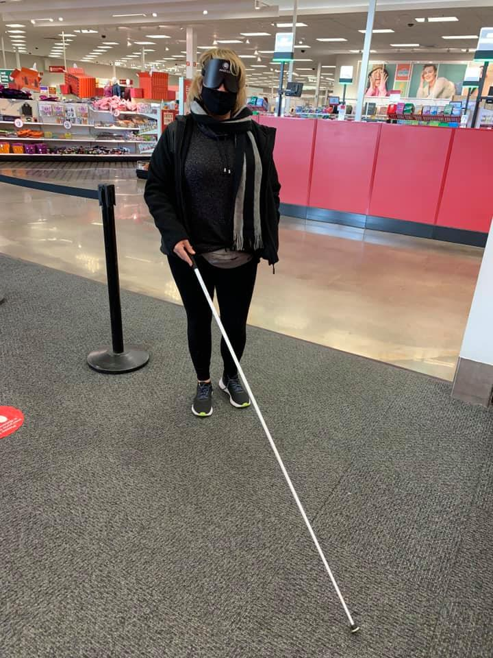 Katie at Target holding her cane and wearing mask and sleep shades during travel class