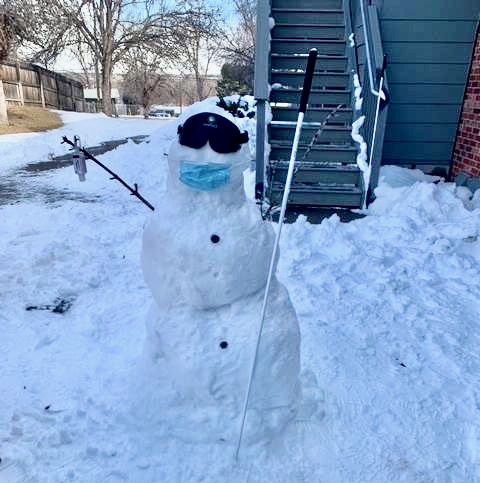 A snow person wearing sleepshades and pandemic mask
