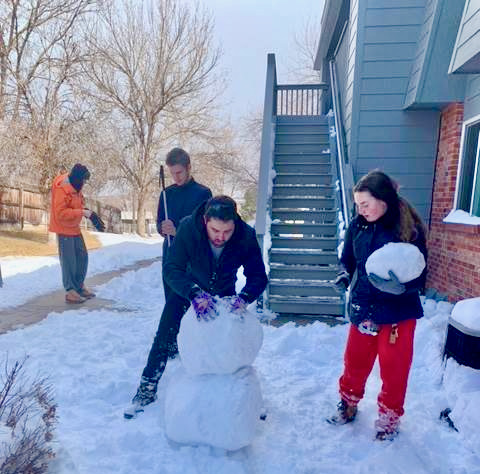a group of students labor in the snow to build a snow person