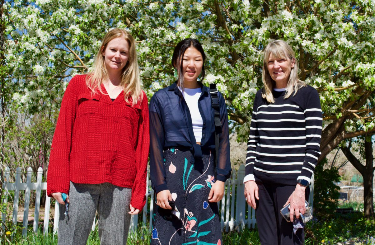 three professional women smile while standing in front of a flowering crab apple tree