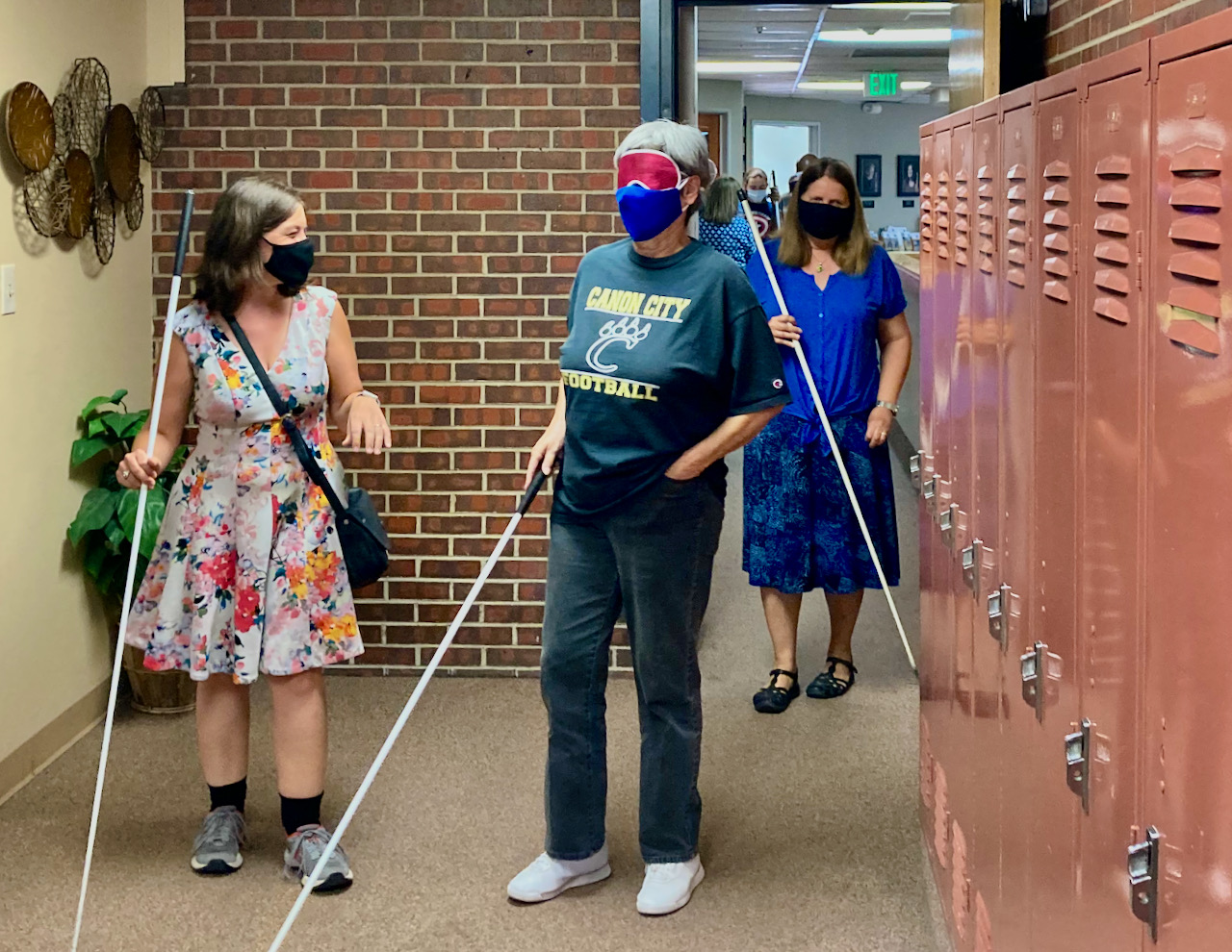 a senior woman navigates the hallway among other students with her instructor following