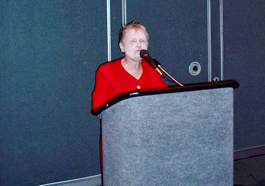 a small well-dressed woman in her 70s stands at a podium, microphone near her face