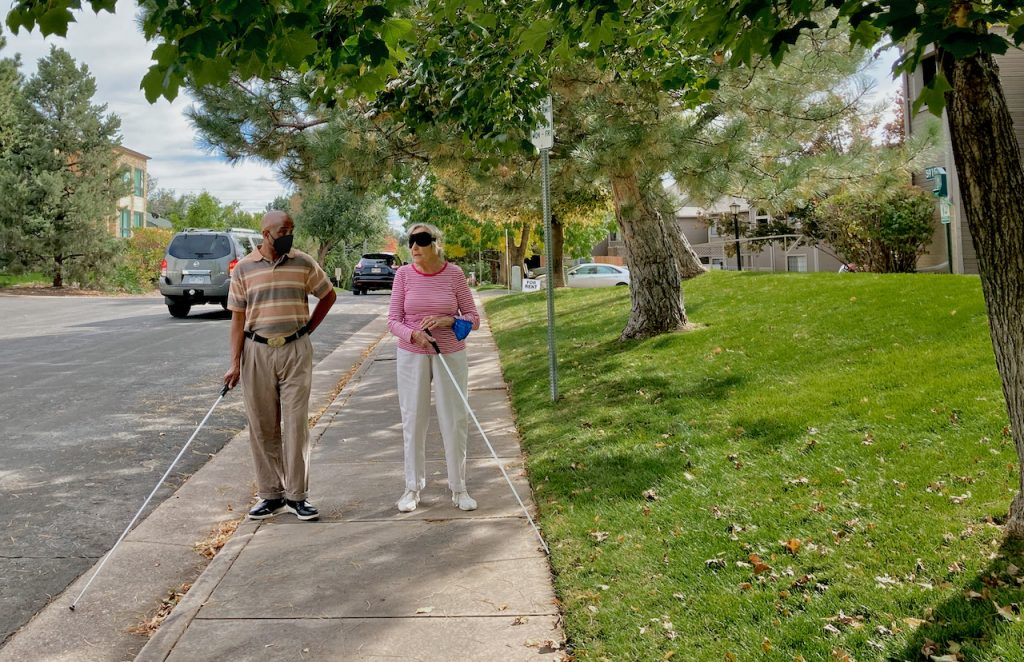 a blind instructor talks with his student, a senior woman as they walk with white canes along a residential street