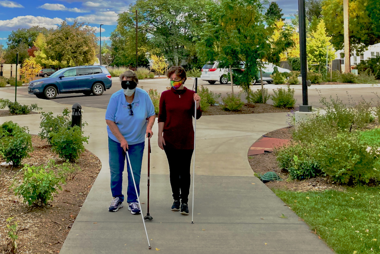 An older woman uses a support cane in her left hand and shorelines on the right with her white cane while her instructor observes